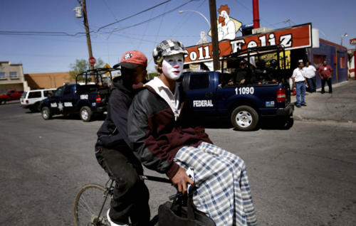 A man, carrying a mime, rides a bicycle past a federal police convoy in Ciudad Juarez, Thursday, April 9, 2009. Drug violence has spiked since President Felipe Calderon began a national crackdown on organized crime in 2006. Battles among cartels, their rivals and soldiers have led to nearly 9,000 deaths and a cross-border crime spillover. (AP Photo/Rodrigo Abd)