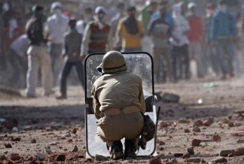 Un poliziotto indiano si protegge con uno scudo dal lancio di pietre dai manifestanti musulmani del Kashmir, a Srinagar 9 settembre 2008. Più di due dozzine di persone tra cui 10 poliziotti sono rimasti feriti nel Kashmir il Martedì, quando la polizia si è scontrata con centinaia di manifestanti in nuova protesta contro il governo indiano nella zona.